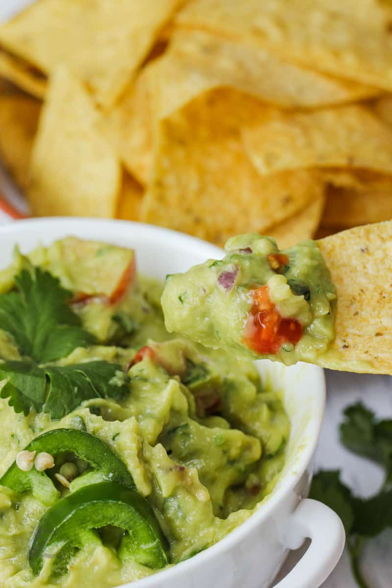 Guacamole with Tomatoes in a bowl with a chip with dip on it