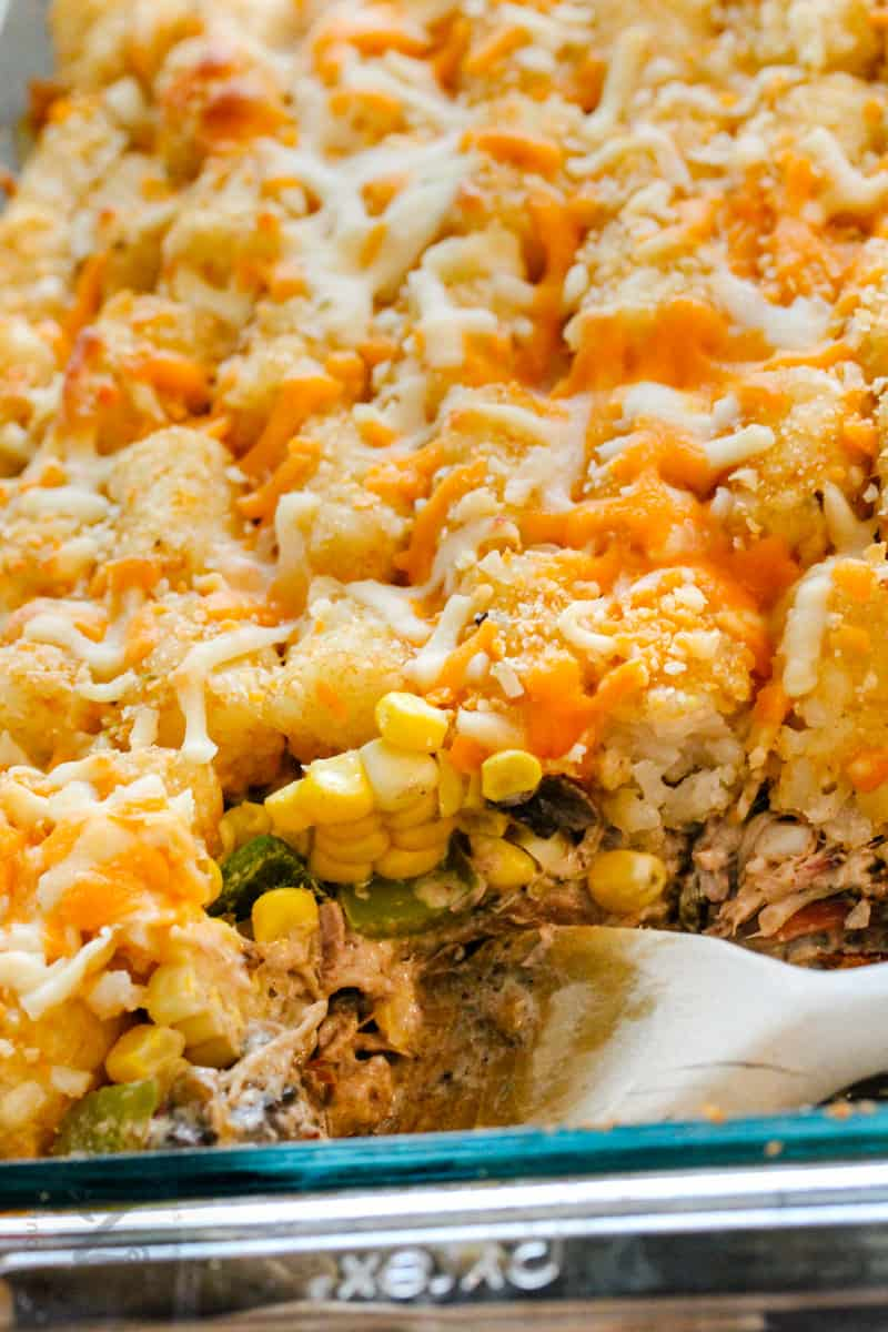 Leftover Pulled Pork Tater Tot Casserole in the dish with a wooden spoon