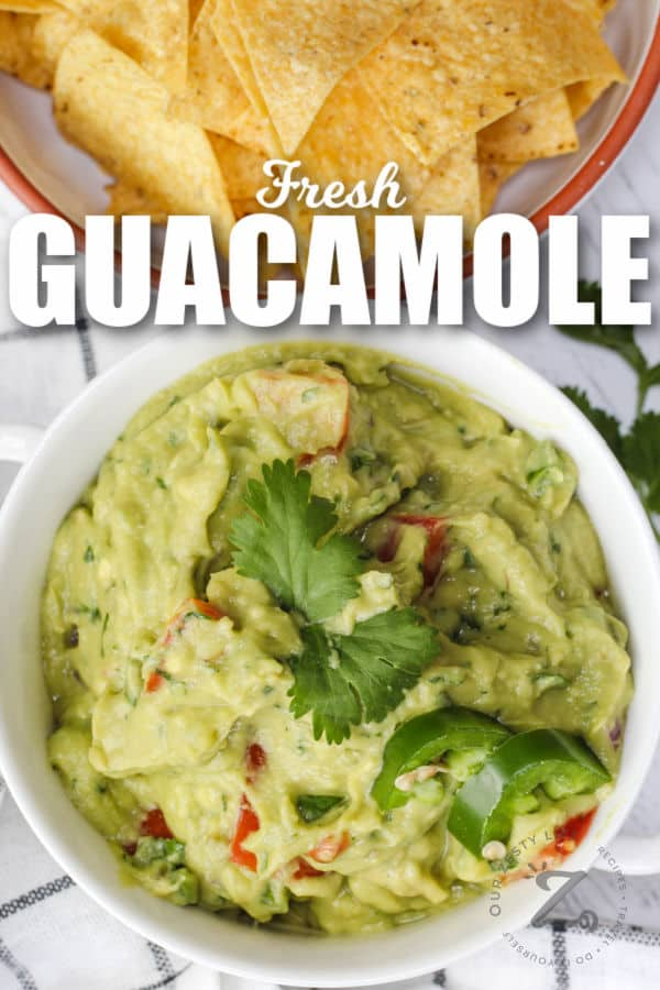bowl of Guacamole with Tomatoes with chips and writing