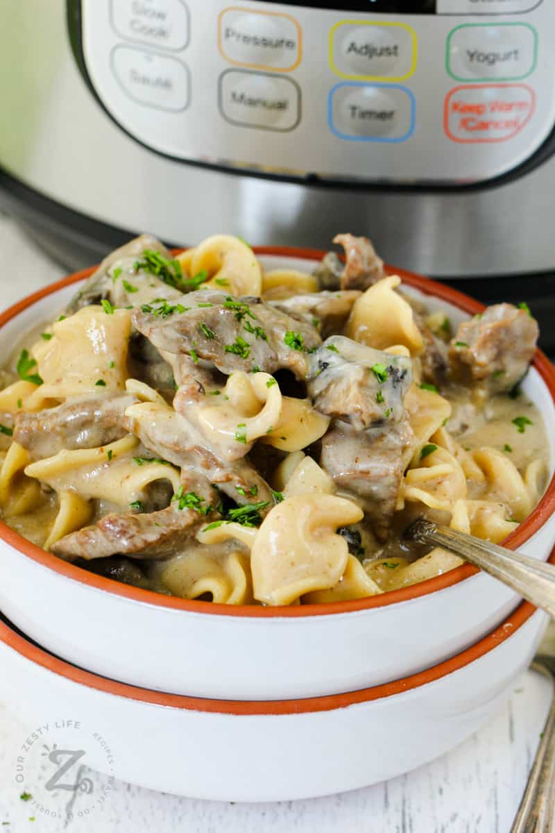 close up of plated Instant Pot Beef Stroganoff with Instant Pot behind it