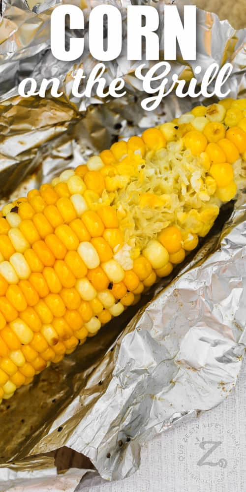 close up of Grilled Corn in Foil with a bite taken out of it with a title