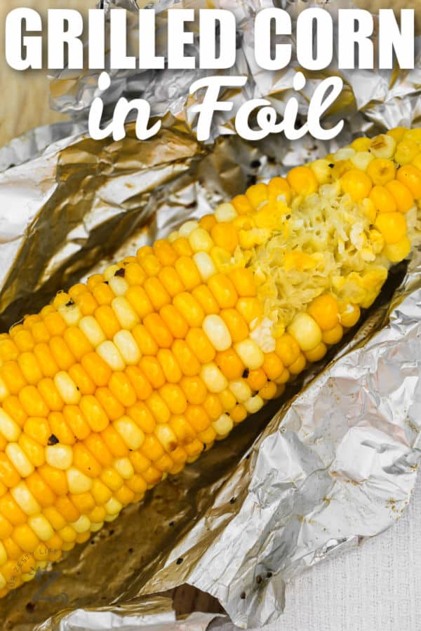 close up of Grilled Corn in Foil with a bite taken out of it with writing