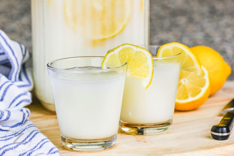 two glasses of Creamy Lemonade with lemons in the back