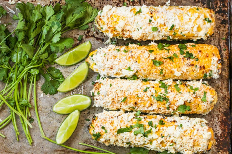 Mexican Street Corn on a baking sheet with lime wedges and cilantro