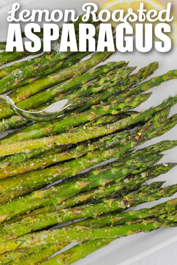 cooked Oven Roasted Asparagus on a plate with lemon and a title