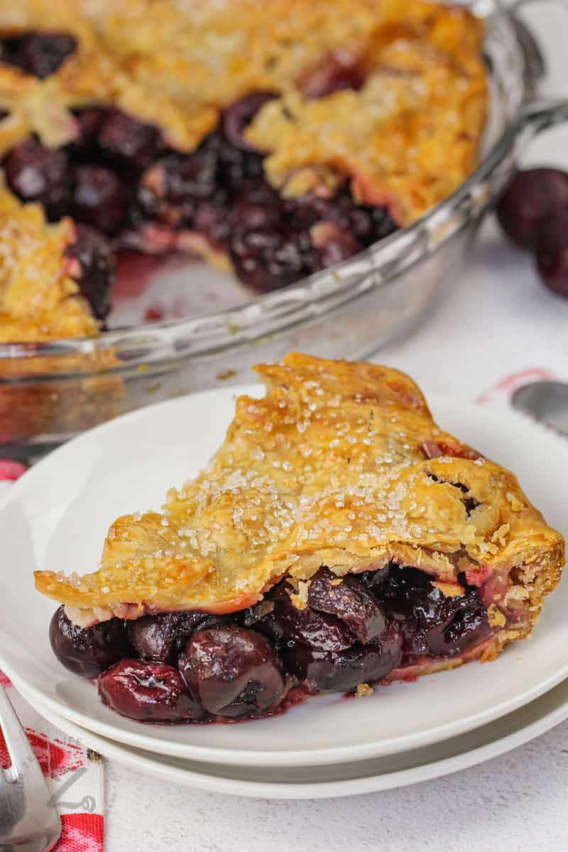 Cherry Pie on a plate with pie in the back