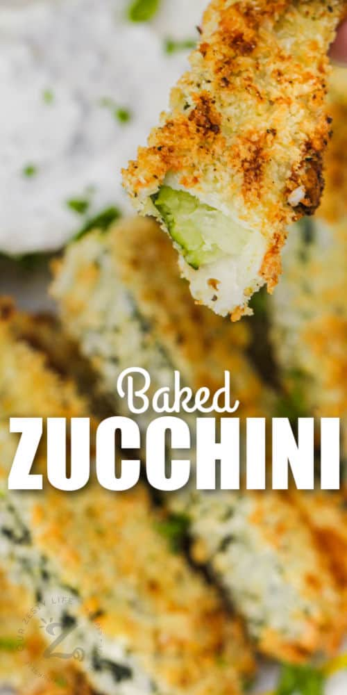 Baked Zucchini Sticks on a plate and a bite taken out of one with writing
